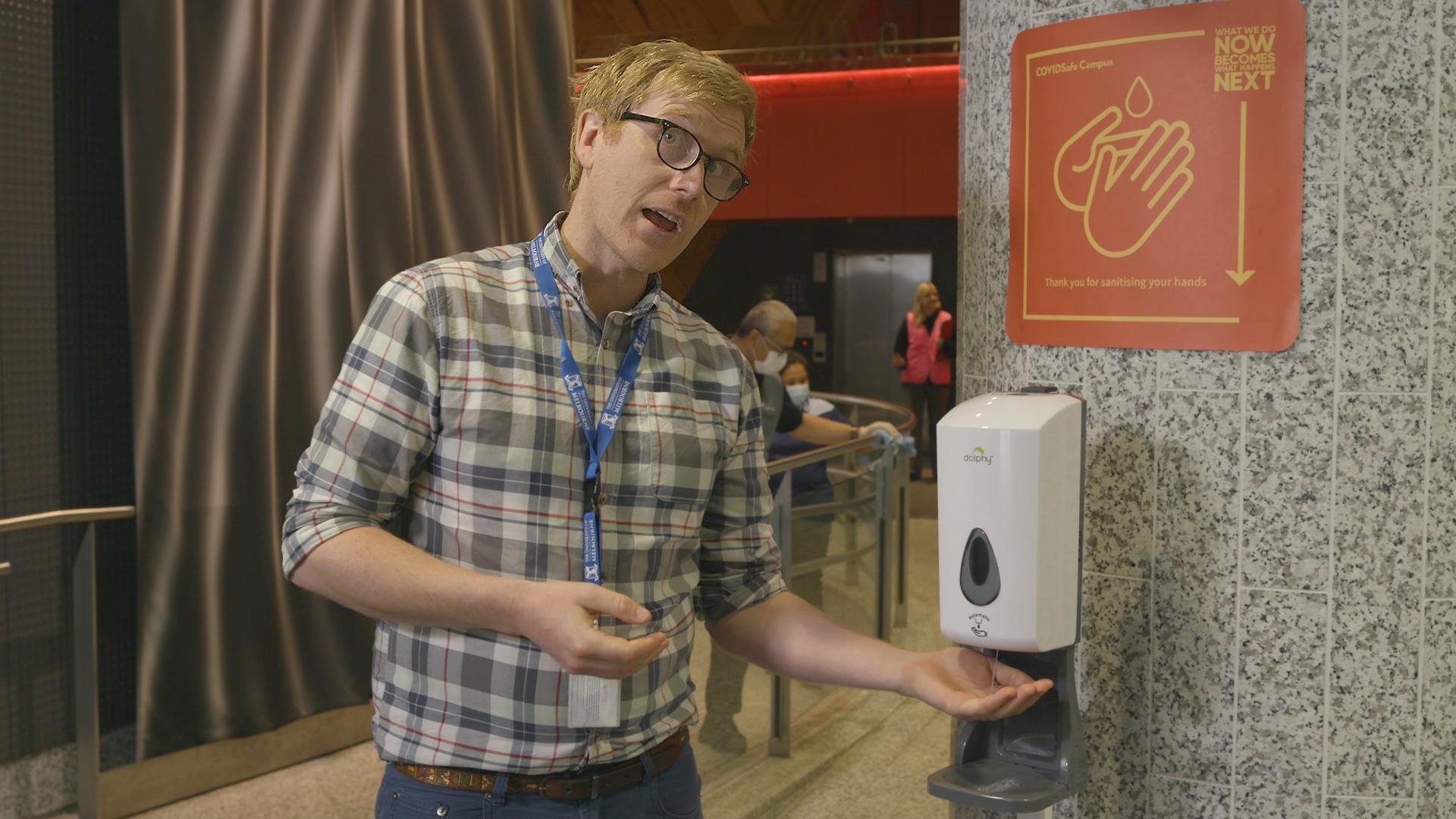 Person using hand sanitiser dispenser