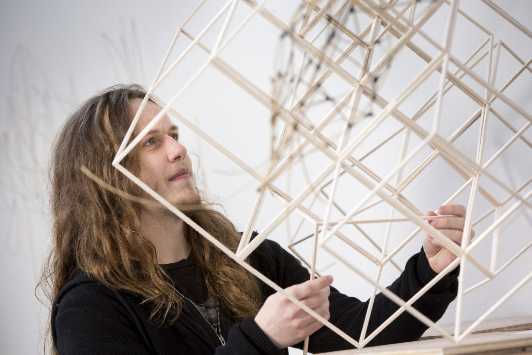 Student holding sculpture