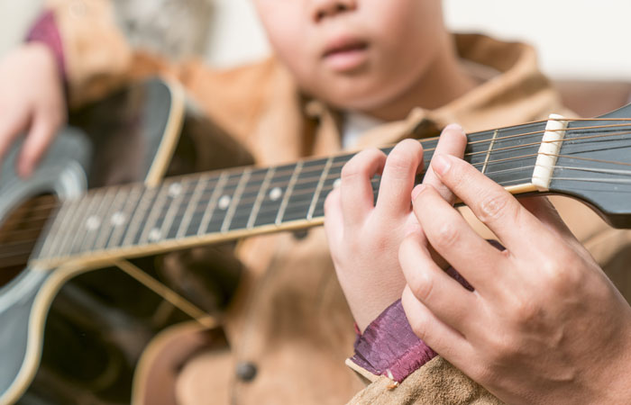 autistic boy playing guitar under guidance