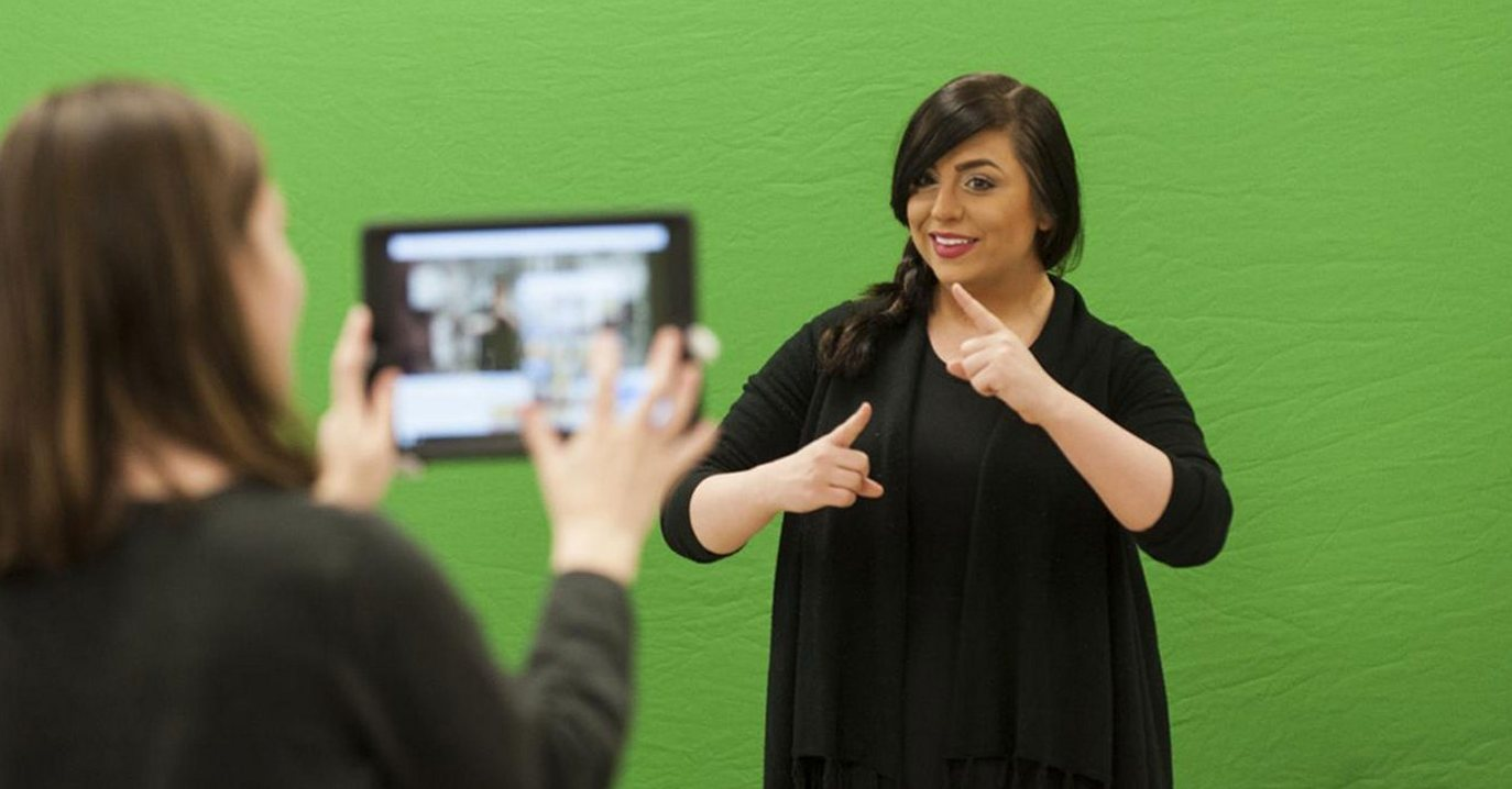 Sign language speaker being recorded on a tablet