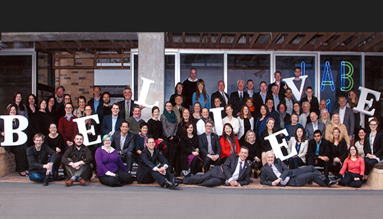 Melbourne University Advancement team holding giant 'Believe' lettering
