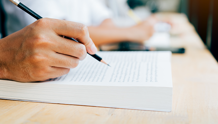 A close-up of someone writing notes on a book