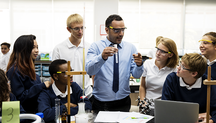 A high school teacher with six students in a science class