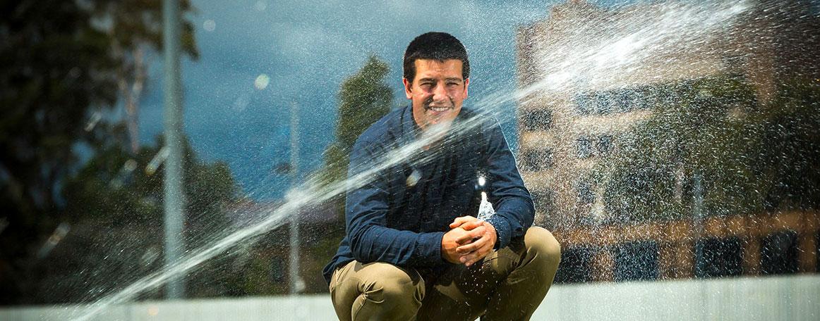 Sam Skinner in front of water spraying